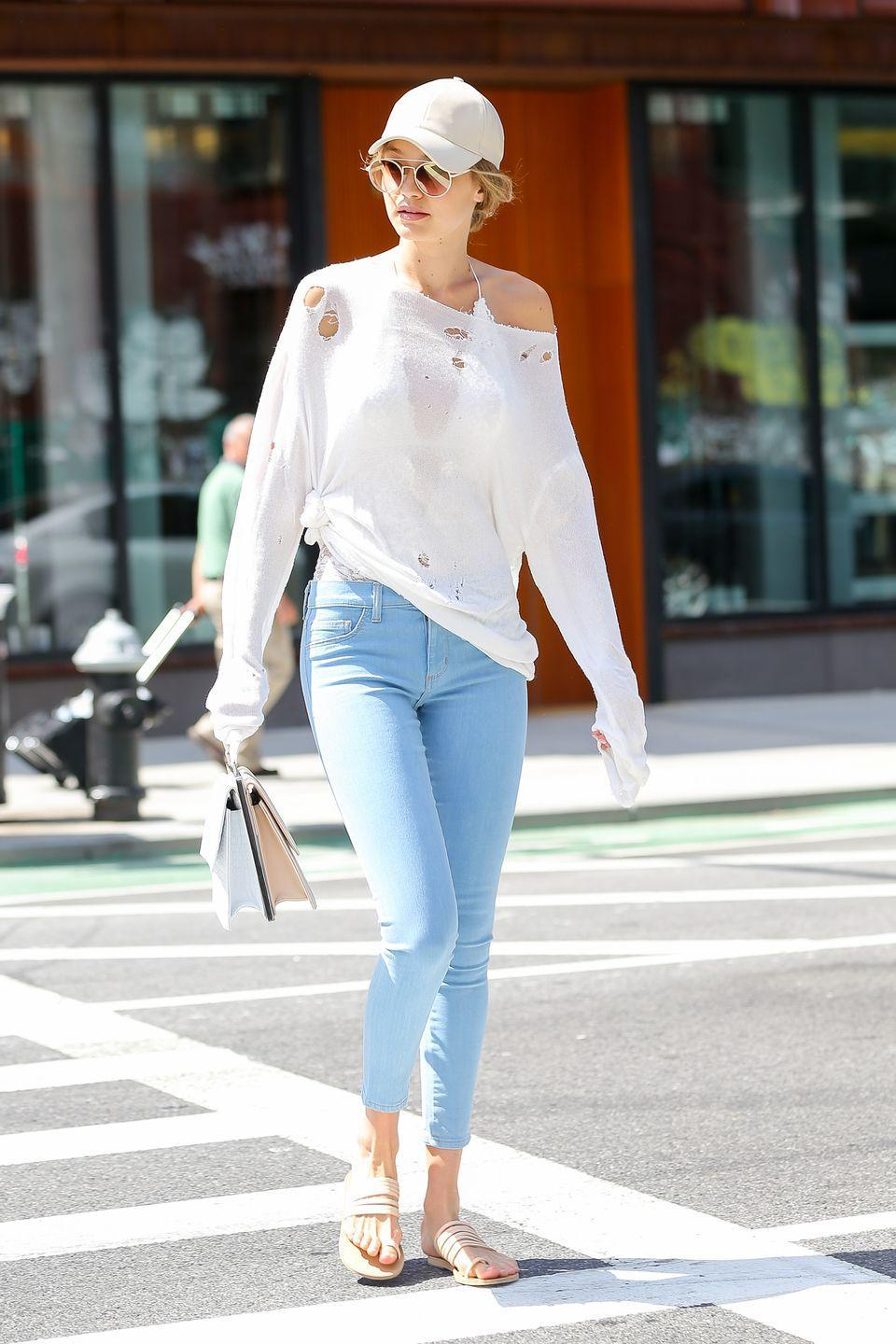 <p>The model steps out to lunch in NYC wearing a distressed white knit and pale blue jeans with flat sandals, a top-handle bag and white baseball cap. </p>