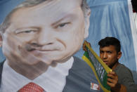 A poster of Turkey's President Recep Tayyip Erdogan is held up during show of support by about a dozen people for Turkey's operation in Syria, in the border town of Akcakale, Sanliurfa province, southeastern Turkey, on Monday, Oct. 14, 2019. Erdogan has criticized NATO allies which are looking to broaden an arms embargo against Turkey over its push into northern Syria. (AP Photo/Lefteris Pitarakis)