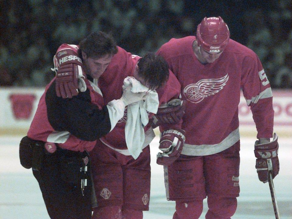 Red Wings forward Kris Draper, center, is helped off the ice by trainer John Wharton, left, teammate Keith Primeau after Draper was hit into the boards from behind by Avalanche forward Claude Lemieux during Game 6 of the Western Conference finals on May 29, 1996, in Denver.