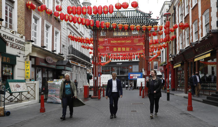 Mayor of London Sadiq Khan, centre, with chefs Angela Hartnett, right and Monica Galetti, walks in China Town central London, Monday, May 17, 2021. Pubs and restaurants across much of the U.K. are opening for indoor service for the first time since early January even as the prime minister urged people to be cautious amid the spread of a more contagious COVID-19 variant. (AP Photo/Alastair Grant)