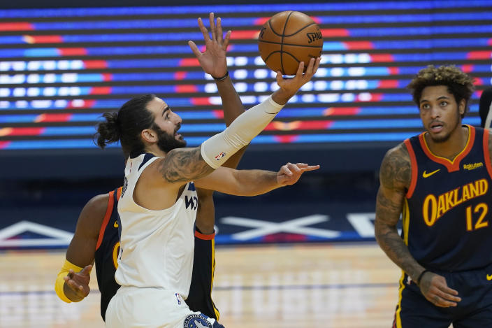 Minnesota Timberwolves guard Ricky Rubio, left, shoots against the Golden State Warriors during the first half of an NBA basketball game in San Francisco, Monday, Jan. 25, 2021. (AP Photo/Jeff Chiu)