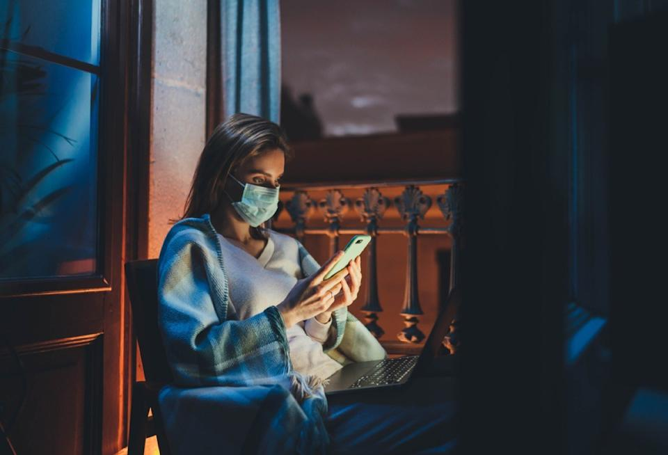 woman with a face mask sitting at a window looking at her phone and computer