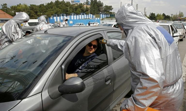 Red Crescent members test people for coronavirus symptoms, as Iranian police blocked Tehran to Alborz highway to check every car