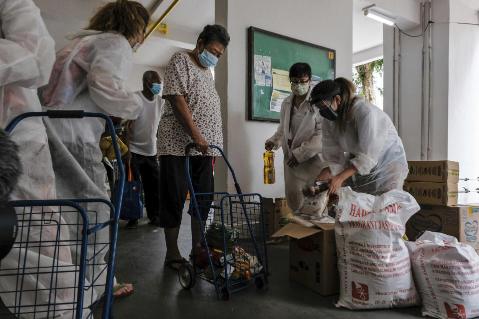Volunteers of Keeping Hope Alive prepare grocery items for a flat resident Sunday, Oct. 4, 2020 in Singapore. Members of the volunteer group conduct weekend door-to-door visits to deliver goods or provide services to people in need. (AP Photo/Ee Ming Toh)