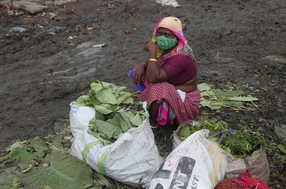 A vendor wearing a face mask as a precaution against the coronavirus waits for customers while selling vegetable leaves at a market in Hyderabad, India, Thursday, Sept. 17, 2020. India's total of coronavirus infections passed 5 million Wednesday, still soaring and testing the feeble health care system in tens of thousands of impoverished towns and villages. (AP Photo/Mahesh Kumar A.)