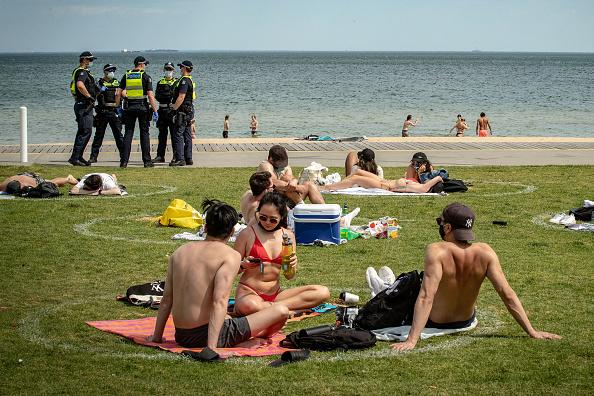 People in Melbourne social distance at the beach.