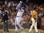 Los Angeles Dodgers' Yasiel Puig (66) celebrates at third base after hitting an RBI triple against the San Francisco Giants in the sixth inning of a baseball game Friday, July 25, 2014, in San Francisco. At left is third base umpire Paul Schrieber, and at right Giants third baseman Pablo Sandoval. (AP Photo)