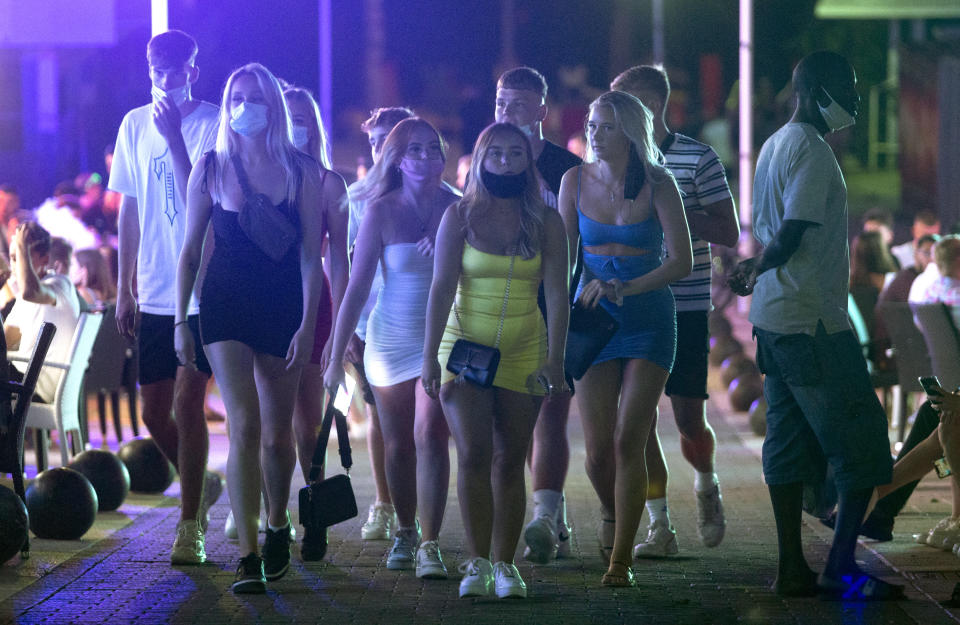 Tourists walk at the resort of Magaluf on the Spanish Balearic island of Mallorca, Spain, Thursday morning, July 16, 2020. Authorities in Spain's Balearic Islands are pulling the plug on endless drunken nights to the beat of techno music by closing bars and nightclubs in beachfront areas popular with young and foreign visitors. (AP Photo/Joan Mateu)
