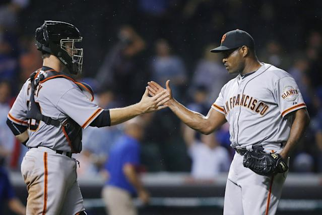San Francisco Giants catcher Buster Posey, left, and relief pitcher Santiago Casilla celebrate after the Giants defeated the Chicago Cubs 5-3 in a baseball game Thursday, Aug. 21, 2014, in Chicago. (AP Photo/Andrew A. Nelles)