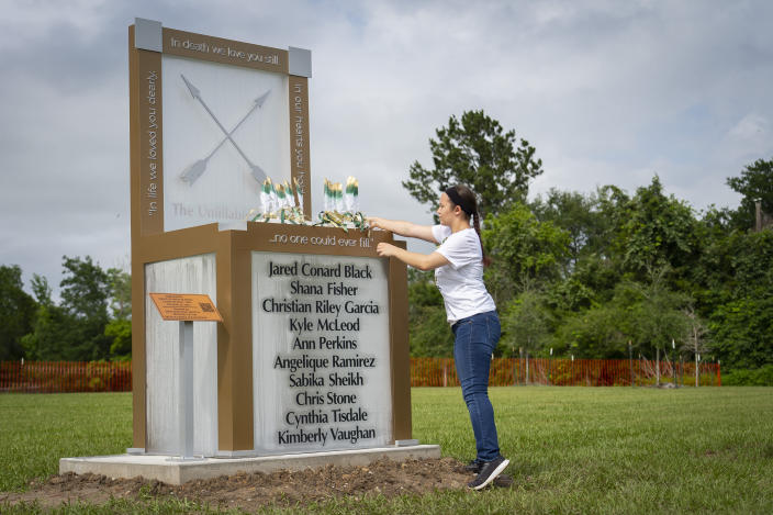 """Morgan Wilson, who will graduate from Santa Fe High School this month, adjusts the ten feathers representing the ten victims of the 2018 Santa Fe school shooting where they sit on a new memorial, Tuesday, May 18, 2021, outside of the high school in Santa Fe, Texas. The Santa Fe Ten Memorial Foundation unveiled the """"Unfillable Chair,"""" a student designed memorial, on the third anniversary of the shooting. The foundation is planning a larger memorial for the future. (Mark Mulligan/Houston Chronicle via AP)"""