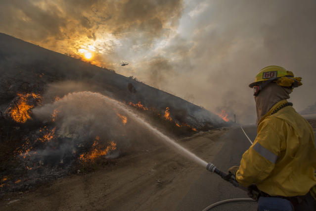 <p>Firefighters use hoses and helicopters to fight the La Tuna fire on Sept. 2, 2017 near Burbank, Calif. (Photo: David McNew/Getty Images) </p>