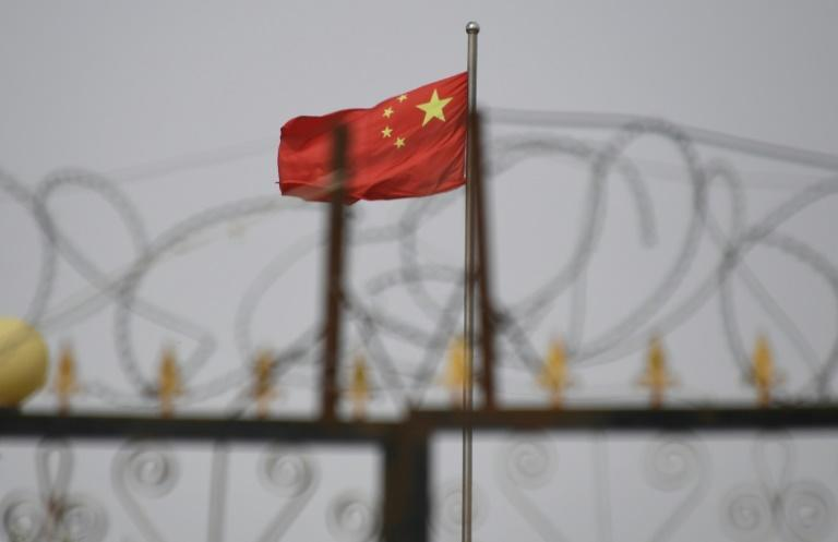 The Chinese flag flies behind razor wire at a housing compound in Yangisar, south of Kashgar, in China's western Xinjiang region (AFP Photo/GREG BAKER)