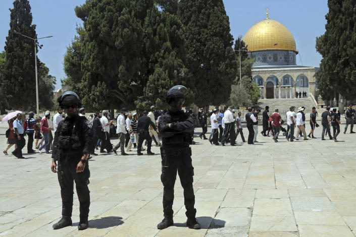 Israeli police officers stand guard as Jewish men visit the Dome of the Rock Mosque in the Al Aqsa Mosque compound, during the annual mourning ritual of Tisha B'Av (the ninth of Av) -- a day of fasting and a memorial day, commemorating the destruction of ancient Jerusalem temples, in the Old City of Jerusalem, Sunday, July 18, 2021. (AP Photo/Mahmoud Illean)