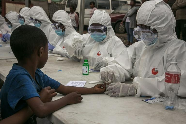 Health workers collect blood from a child to detect coronavirus, in Antananarivo, Madagascar