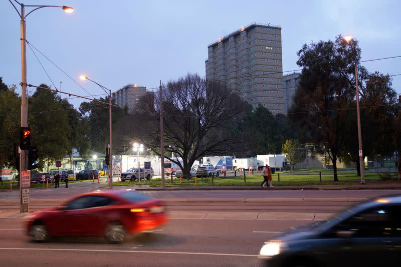 Vehicles drive past public housing towers locked down in response to a COVID-19 outbreak in Melbourne