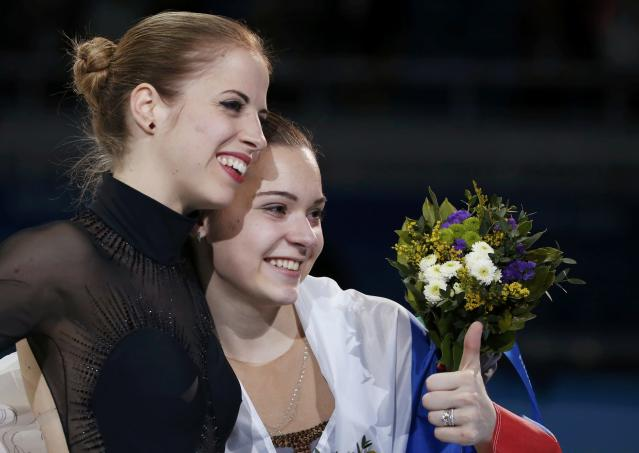 Russia's Adelina Sotnikova (R) and Italy's Carolina Kostner celebrate after the flower ceremony during the Figure Skating Women's free skating Program at the Sochi 2014 Winter Olympics, February 20, 2014. REUTERS/Lucy Nicholson (RUSSIA - Tags: OLYMPICS SPORT FIGURE SKATING)