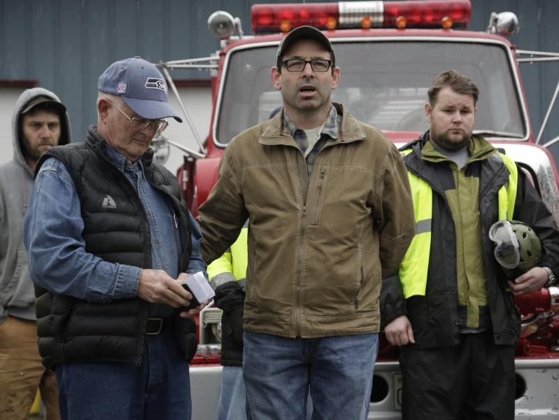 Darrington Mayor Dan Rankin (2nd R) and Pastor Mike De Luca (2nd L) lead workers and community members in prayer and a moment of silence marking the one-week anniversary of the Oso landslide at the fire station in Darrington, Washington March 29, 2014. The grim task of combing through debris from a mudslide that obliterated dozens of homes on the outskirts of a rural Washington town came to a standstill briefly on Saturday for a moment of silence. The somber moment at 10:37 a.m. (1737 GMT) was observed exactly one week after the catastrophe, amid uncertainty over the fate of 90 people still listed as missing. On Friday, the body count was at 27. REUTERS/Jason Redmond (UNITED STATES - Tags: DISASTER ENVIRONMENT POLITICS)