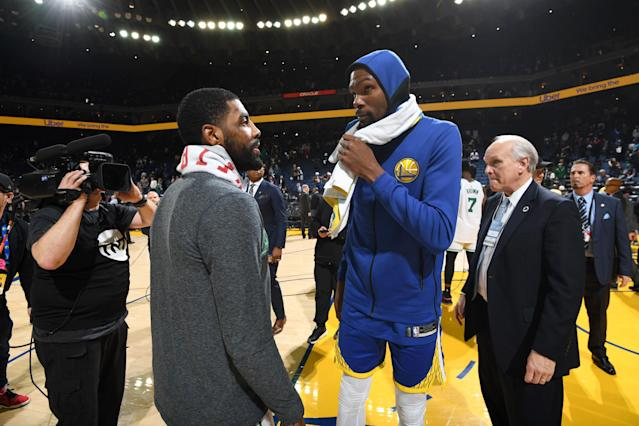 Kyrie Irving, left, and Kevin Durant, who will be free agents this summer, talk after Tuesday night's game. (Getty Images)