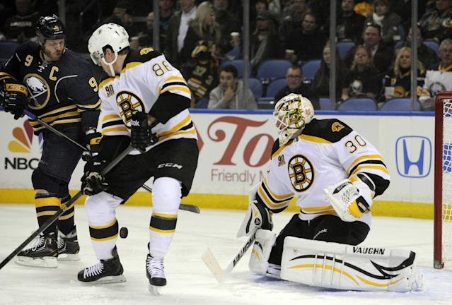Buffalo Sabres' Steve Ott (9) battles for a rebound as Boston Bruins' Kevan Miller (86) and Chad Johnson (30) defend during the first period of an NHL hockey game in Buffalo, N.Y., Wednesday, Feb. 26, 2014. (AP Photo/Gary Wiepert)