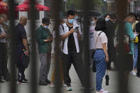 FILE - In this June 9, 2021, file photo, a man wearing a face mask to help curb the spread of the coronavirus browses his smartphone lining up with masked residents to receive their vaccine at a vaccination point at the Central Business District in Beijing. Chinese President Xi Jinping pledged 2 billion doses of Chinese vaccines would be supplied to the world through this year and $100 million would be donated to a U.N.-backed distribution program, state media reported. (AP Photo/Andy Wong, File)