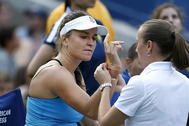 Alexandra Dulgheru, left, of Romania, receives medical treatment from the trainer during the third set of her match against Maria Sharapova, of Russia, during the second round of the U.S. Open tennis tournament Wednesday, Aug. 27, 2014, in New York. (AP Photo/Jason DeCrow)