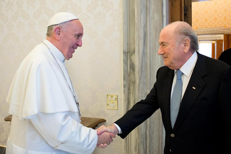 """In this photo provided by the Vatican newspaper L'Osservatore Romano Pope Francis shakes hands with FIFA president Joseph Sepp Blatter, left, during their meeting at the Vatican Friday, Nov. 22, 2013. """"We spoke the same language and it was language of football,"""" Blatter said during a press conference following the meeting, ' It was really a meeting between two sportsmen and two football fans.""""(AP Photo/L' Osservatore Romano, ho)"""