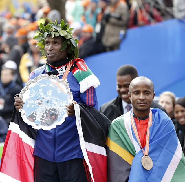 New York City marathon winner Geoffrey Mutai of Kenya, left, holds his trophy, and third place finisher Lusapho April stands with him on the medal stand after they compeleted the New York City marathon, Sunday, Nov. 3, 2013, in New York. (AP Photo/Kathy Willens)