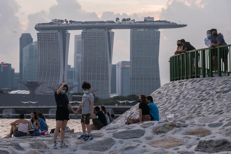 People wearing masks relax on a breakwater with the Marina Bay Sands in the background in Singapore on Sunday, 6 June, 2021. The current phase of social distancing restrictions that are due to  be lifted on 13 June 2021 were enacted after a spike in local COVID-19 cases at the start of May 2021. Some of these restrictions disallow dining in at all food establishments and limit social interaction to groups not larger than 2. (Photo by Joseph Nair/NurPhoto via Getty Images)
