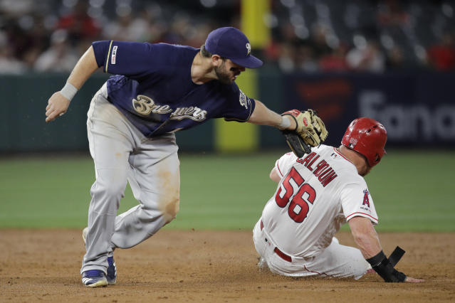 Los Angeles Angels' Kole Calhoun, right, is caught stealing second base by Milwaukee Brewers' Mike Moustakas during the third inning of a baseball game, Monday, April 8, 2019, in Anaheim, Calif. (AP Photo/Jae C. Hong)