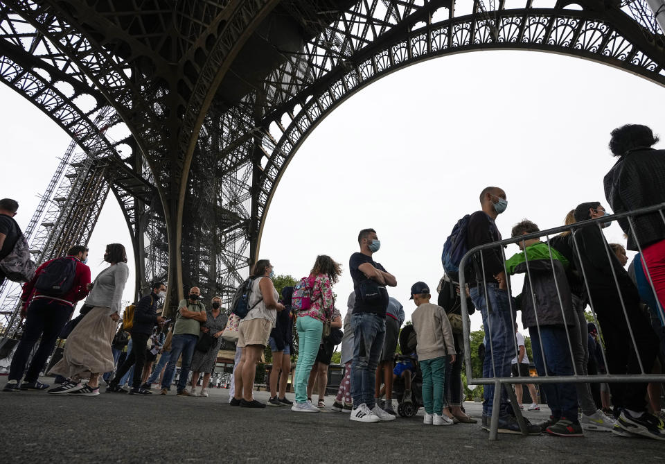 """Visitor line up at the Eiffel Tower in Paris, Friday, July 16, 2021. The Eiffel Tower is reopening Friday for the first time in nine months, just as France faces new virus rules aimed at taming the fast-spreading delta variant. The """"Iron Lady"""" was ordered shut in October as France battled its second surge of the virus. (AP Photo/Michel Euler)"""
