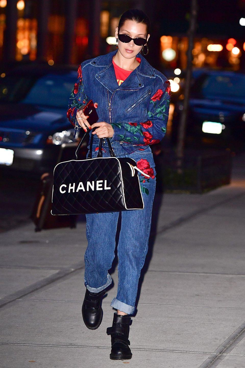<p>In red t-shirt under an embroidered Adam Selman moto jacket with matching jeans, a Chanel duffel bag, Dr. Martens boots and black sunglasses while out in New York City. </p>