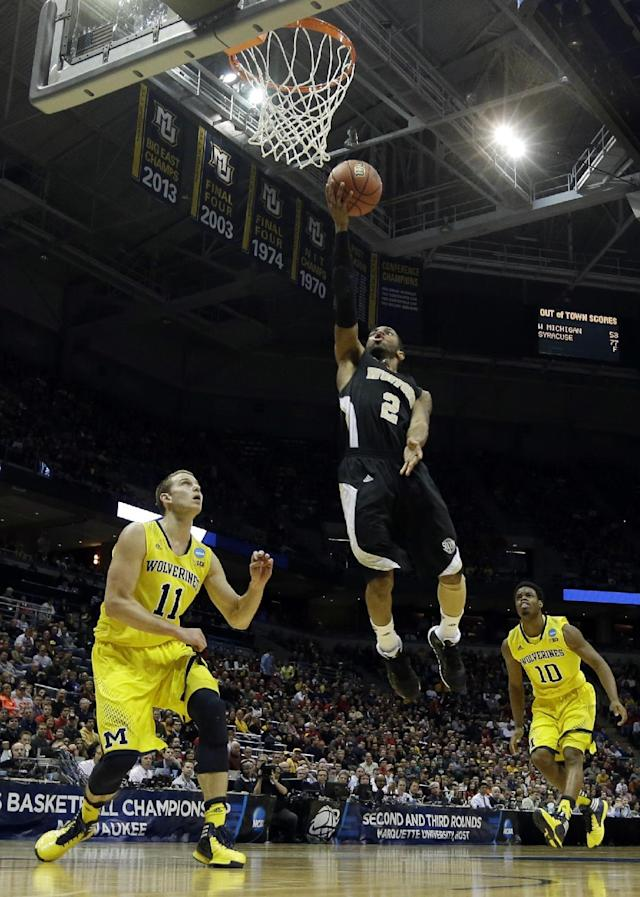Wofford guard Karl Cochran (2) drives to the basket against Michigan guard Nik Stauskas (11) during the second half of a second round NCAA college basketball tournament game against the Michigan Thursday, March 20, 2014, in Milwaukee. At right is Michigan guard Derrick Walton Jr. (10). (AP Photo/Morry Gash)