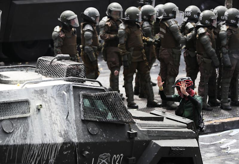 A demonstrator gestures in front of an armored vehicle during a protest against Chile's state economic model in Santiago, Chile on Oct. 23, 2019. (Photo: Ivan Alvarado/Reuters)