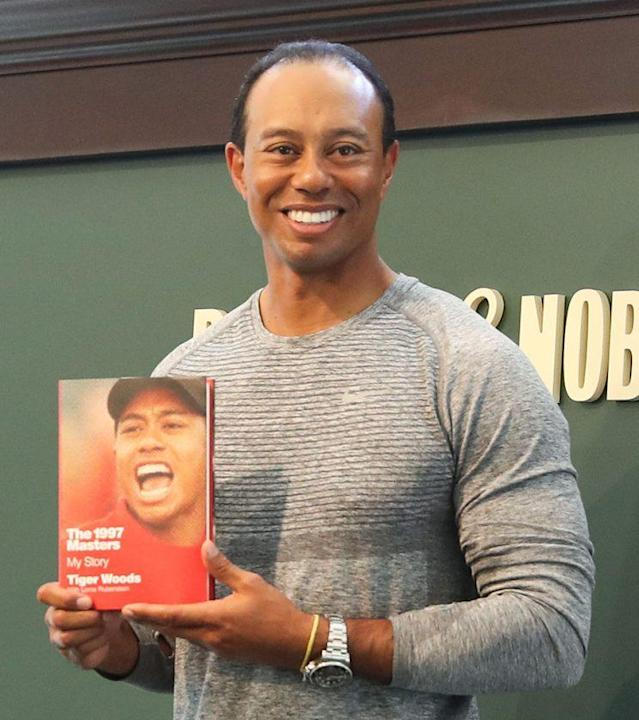 "Tiger Woods signs copies of his new book, ""The 1997 Masters: My Story,"" on March 20. (Photo: Rob Kim/Getty Images)"