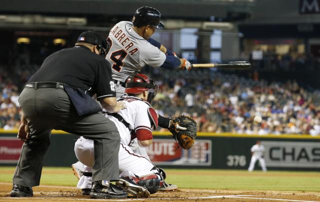 Detroit Tigers' Miguel Cabrera, top, connects on a run-scoring single as Arizona Diamondbacks' Miguel Montero, bottom right, and umpire Fieldin Culbreth, left, look on during the first inning of a baseball game on Tuesday, July 22, 2014, in Phoenix. (AP Photo)