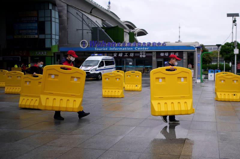 Staff members move barriers in front of a railway station of Wuhan on the first day of inbound train services resumed following the novel coronavirus disease (COVID-19) outbreak, in Wuhan