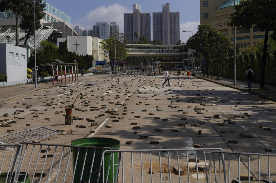 People walk by a road scattered with bricks and barricades set by pro-democracy protesters outside the Hong Kong Baptist University, in Hong Kong, Wednesday, Nov. 13, 2019. Police have increased security around Hong Kong and its university campuses as they brace for more violence after sharp clashes overnight with anti-government protesters. (AP Photo/Vincent Yu)