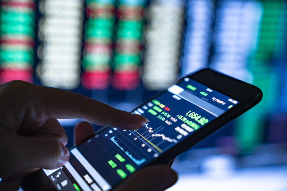 Close-up of hands of businesswoman looking at stock market charts and key performance indicators on her smartphone
