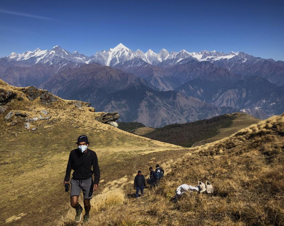 People wearing face masks trek up to Khalia top as snow clad Himalayan ranges of Panchchuli mountains are seen behind near Munsiyari in the Indian state of Uttarakhand, Thursday Oct. 29, 2020. India's confirmed coronavirus caseload surpassed 8 million on Thursday with daily infections dipping to the lowest level this week, as concerns grew over a major Hindu festival season and winter setting in. ( AP Photo/Manish Swarup)