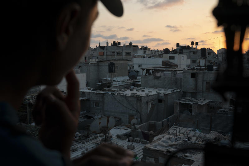 In this Sept. 12, 2018, photo, a boy looks out of the window as the sun sets in Gaza City. Ever since Hamas launched demonstrations in March against Israel's blockade of Gaza, children have been a constant presence in the crowds. Since then, U.N. figures show that 948 children under 18 have been shot by Israeli forces and 2,295 have been hospitalized, including 17 who have had a limb amputated. (AP Photo/Felipe Dana)