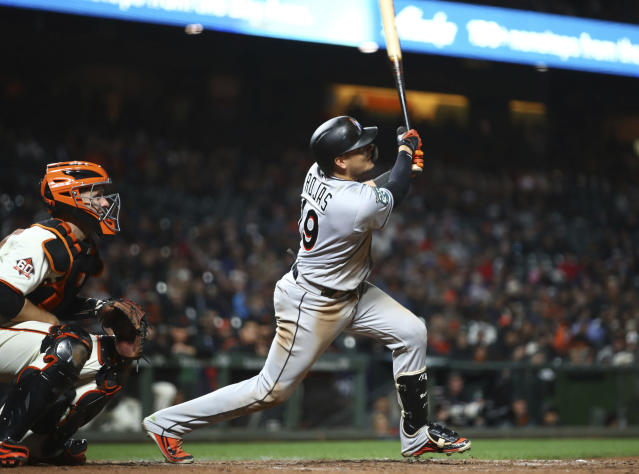 Miami Marlins' Miguel Rojas swings for an RBI single off San Francisco Giants' Hunter Strickland in the ninth inning of a baseball game Monday, June 18, 2018, in San Francisco. (AP Photo/Ben Margot)
