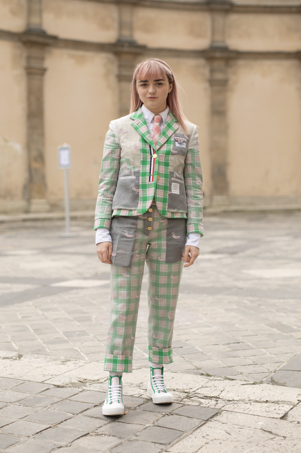 <p>Maisie Williams wore a green and pink Thom Browne suit with matching high top trainers at the label's AW19 show during Paris Fashion Week. <em>[Photo: Getty]</em> </p>