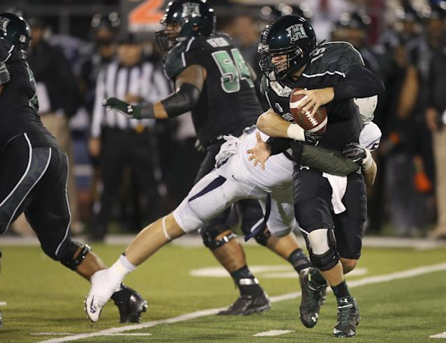 Hawaii's Sean Schroeder (19) gets sacked by Nevada's Brock Hekking during the second half of an NCAA college football game in Reno, Nev., on Saturday, Sept. 21, 2013. (AP Photo/Cathleen Allison)