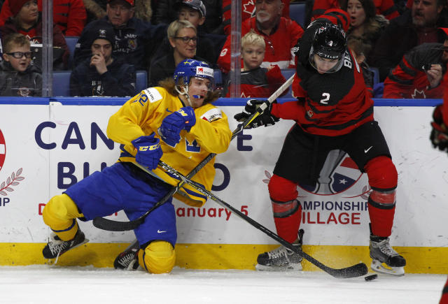 Canada defenseman Jake Bean and Sweden forward Axel Jonsson Fjallby collide during the first period in the gold medal game of the world junior hockey championships, Friday, Jan. 5, 2018 (AP Photo/Jeffrey T. Barnes)