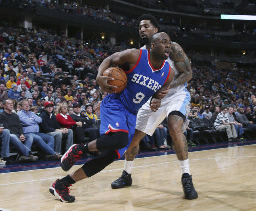 Philadelphia 76ers guard James Anderson, front, drives for shot past Denver Nuggets forward Wilson Chandler during the first quarter of an NBA basketball game in Denver on Wednesday, Jan. 1, 2014. (AP Photo/David Zalubowski)