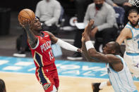 New Orleans Pelicans guard Kira Lewis Jr. (13) looks to shoot over Charlotte Hornets center Bismark Biyombo during the first half of an NBA basketball game Sunday, May 9, 2021, in Charlotte, N.C. (AP Photo/Brian Westerholt)
