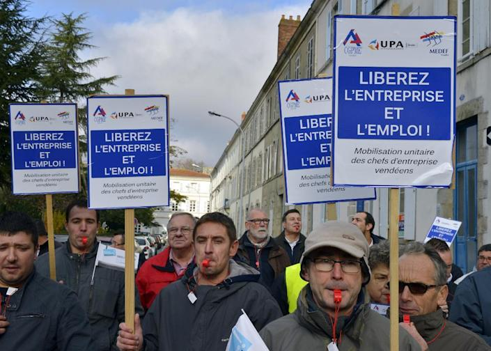 Demonstrators blow whistles and carry banners at a protest in La Roche-sur-Yon on December 5, 2014 against the government's economic policies (AFP Photo/Georges Gobet)
