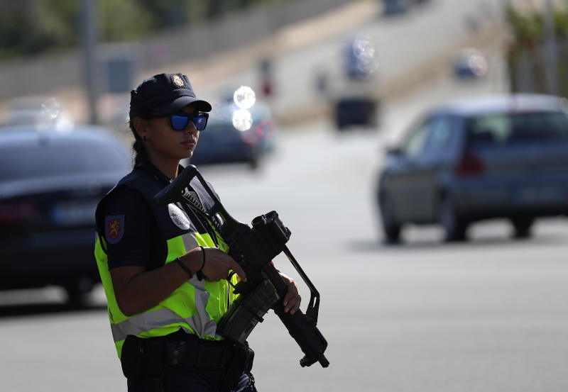 Spanish and French police officers stand guard at the border between Hendaye and Irun to monitor protestors against the G-7 summit in nearby Biarritz, France Friday, Aug. 23, 2019. (AP Photo/Emilio Morenatti)