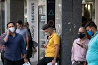 Iranian men check their smartphones in front of a shopping mall in northern Tehran on June 19, 2021
