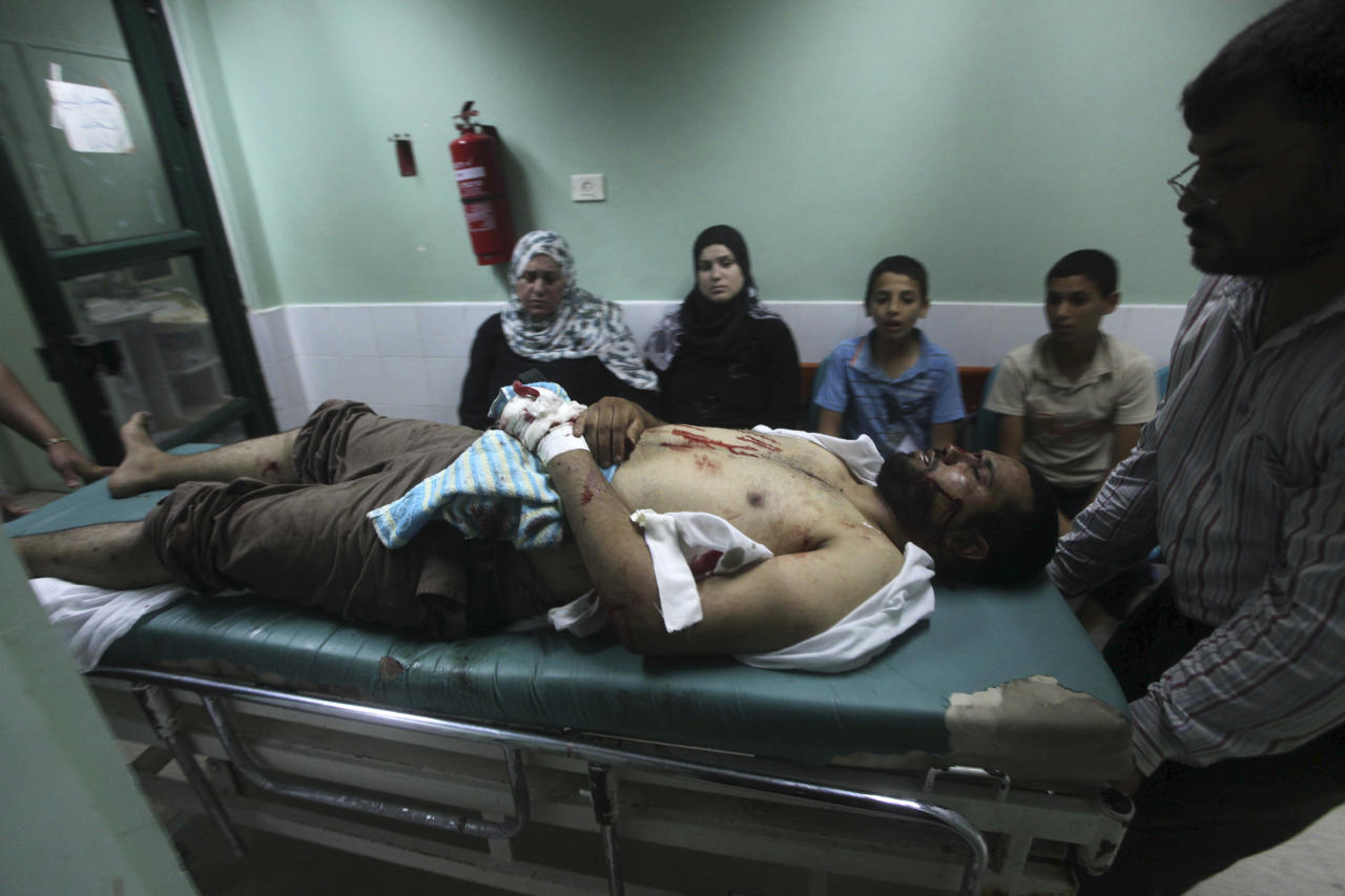 Palestinian medics wheel a wounded man to the treatment room of Al-Aqsa hospital following an Israeli airstrike east of Bureij refugee camp, in Deir Al Balah, central Gaza strip, Friday, June 22, 2012. (AP Photo/Ashraf Amra)